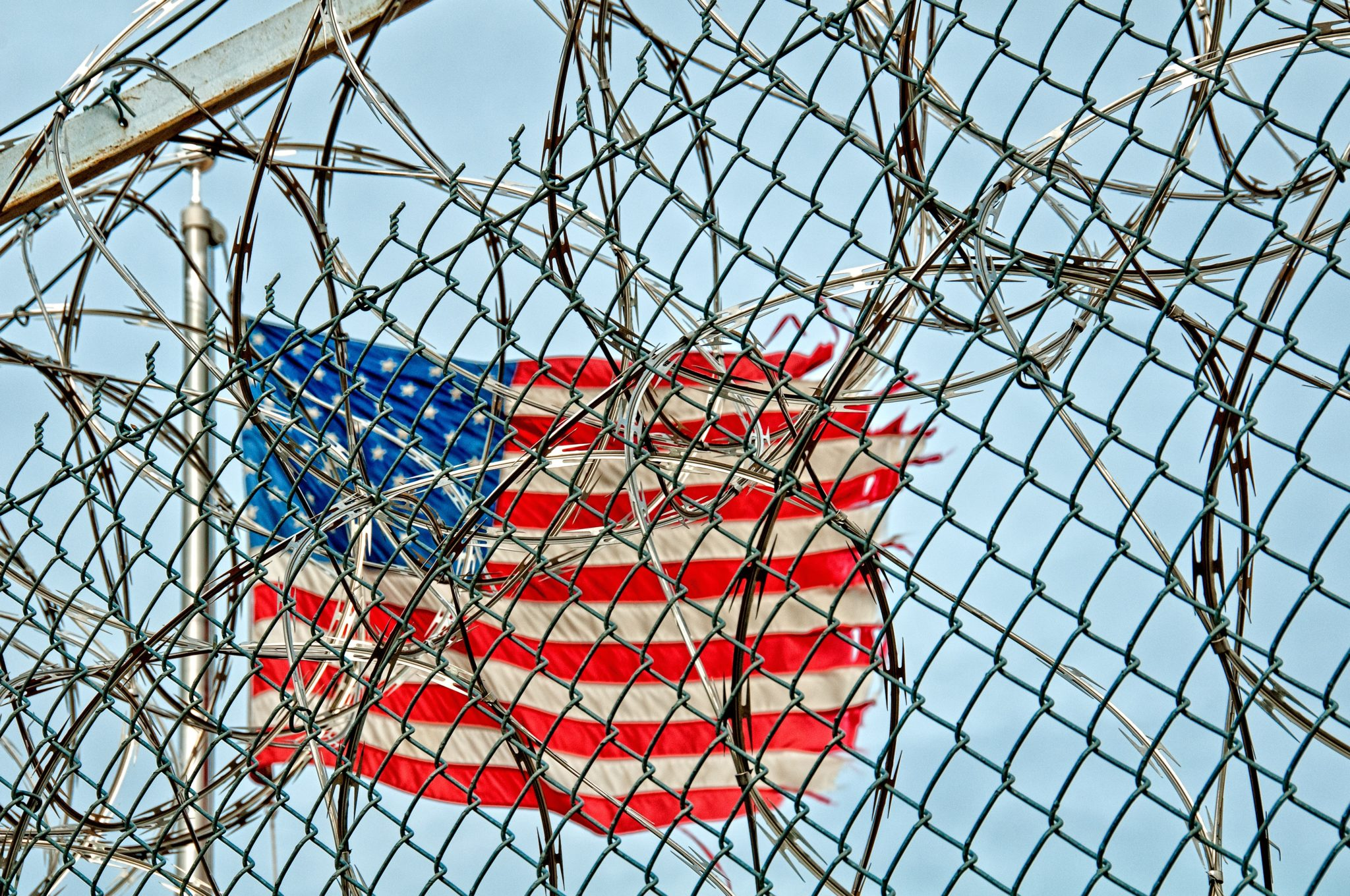 American flag behind barbed wire fence | Teenzone